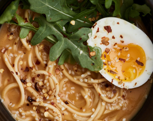 Black bowl filled with noodles, orange broth, arugula, and an egg sliced in half on a light grey background