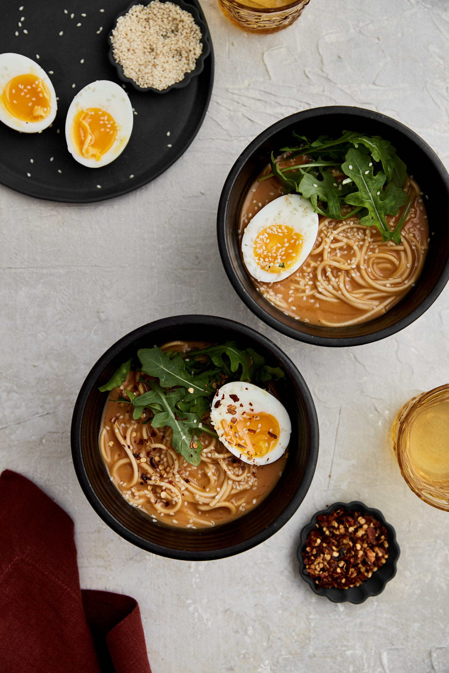 two black bowls of noodles in broth topped with arugula and cut-open soft-boiled eggs.