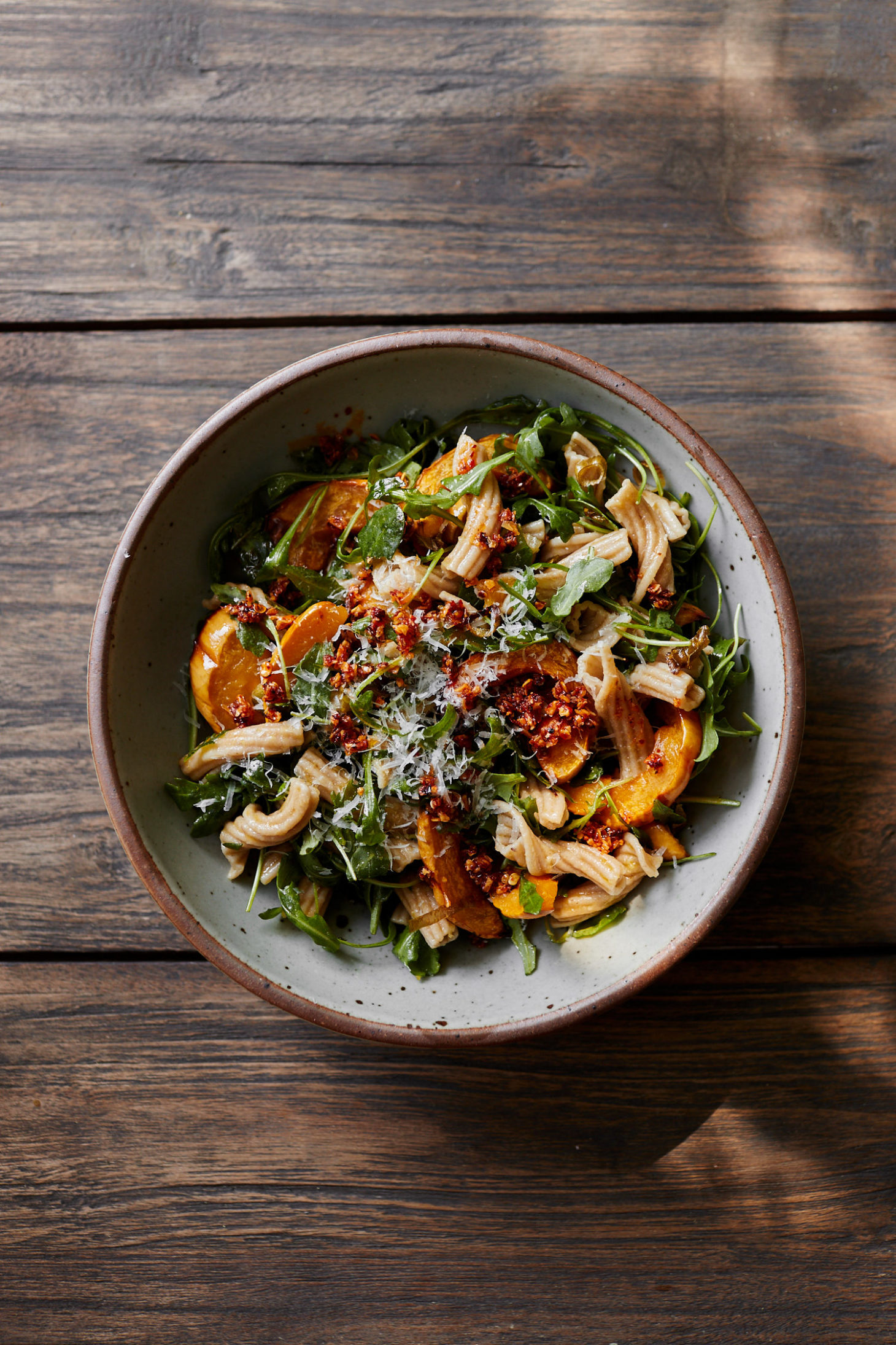 Image of a grey bowl on a light wood table filled with arugula, delicata squash, and pasta.
