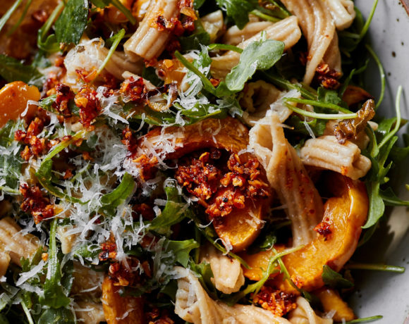 Close-up image of pasta with arugula and delicata squash.