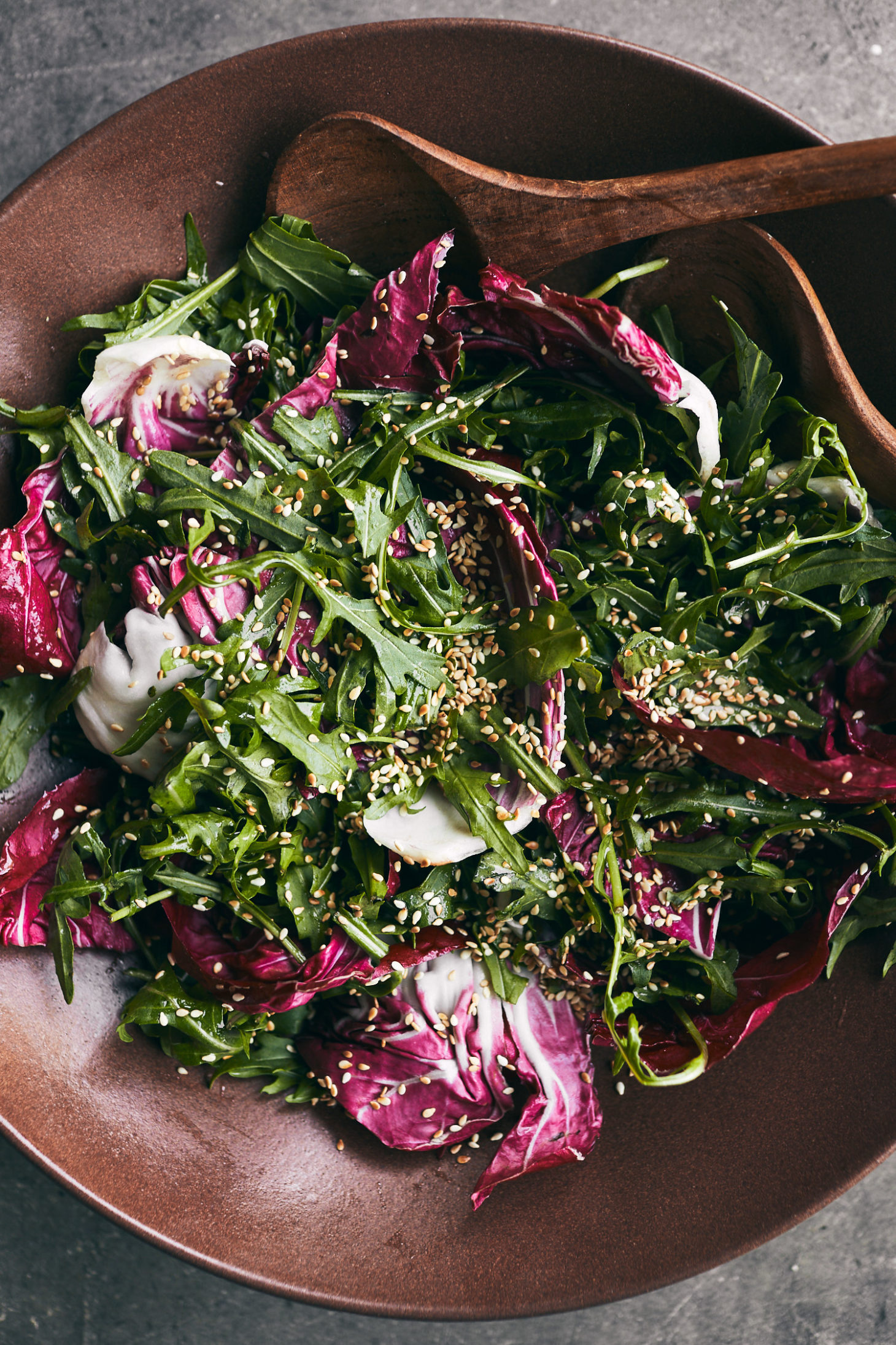 close-up of a brick colored bowl filled with arugula, radicchio, and sesame seeds.