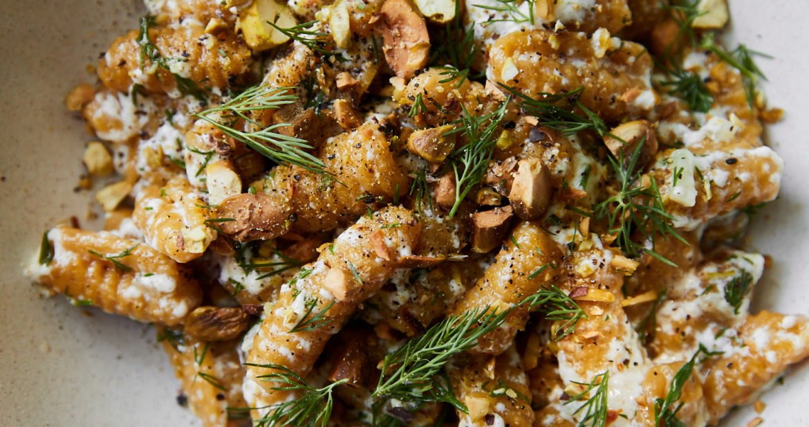Close-up photo of orange cavatelli in a white bowl topped with ricotta and dill.
