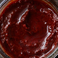 Close-up of a reddish paste in a clear jar.