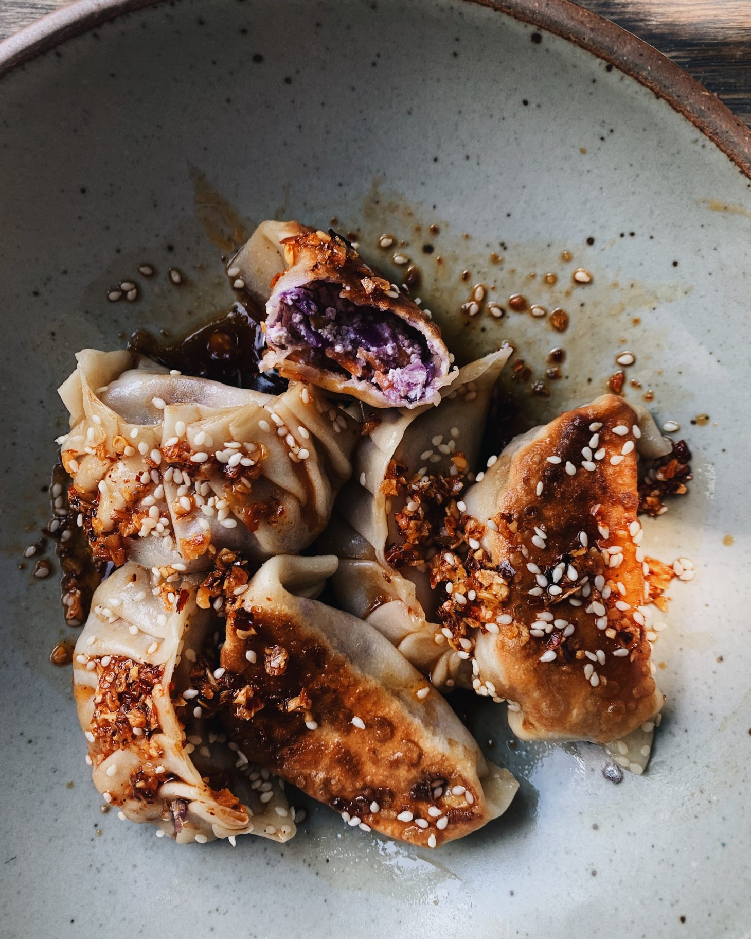 Close-up photo of potstickers with one open to reveal purple filling.