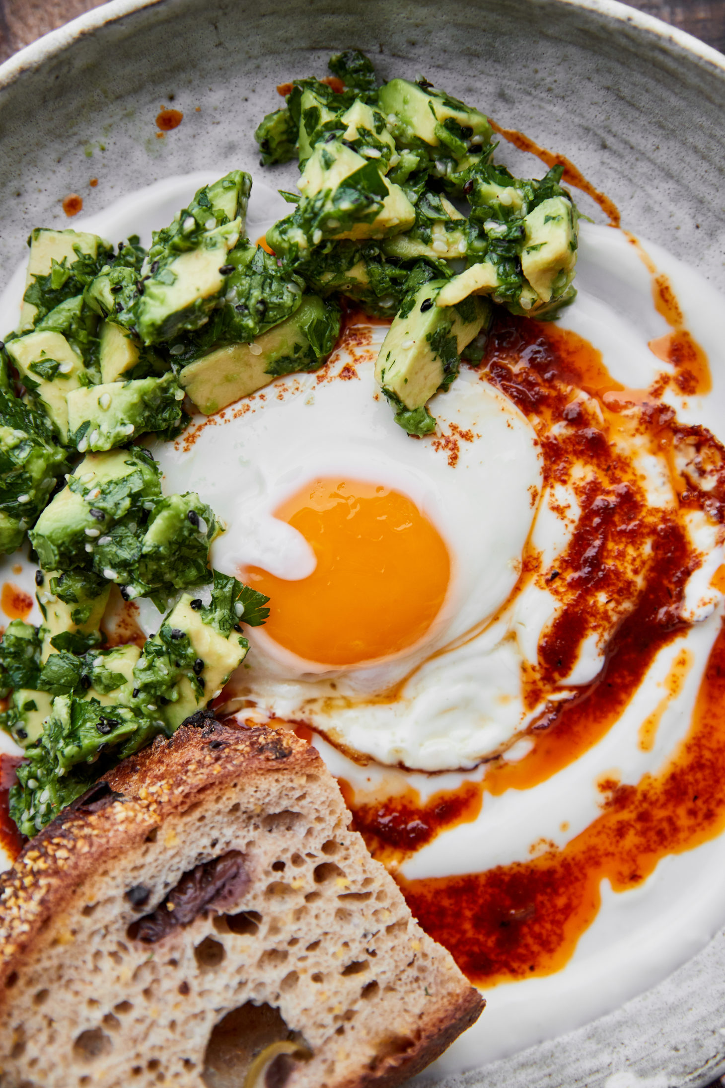 Close-up of a sunny-side egg on top of yogurt and topped with a fiery red butter sauce and diced avocado tossed in herbs.
