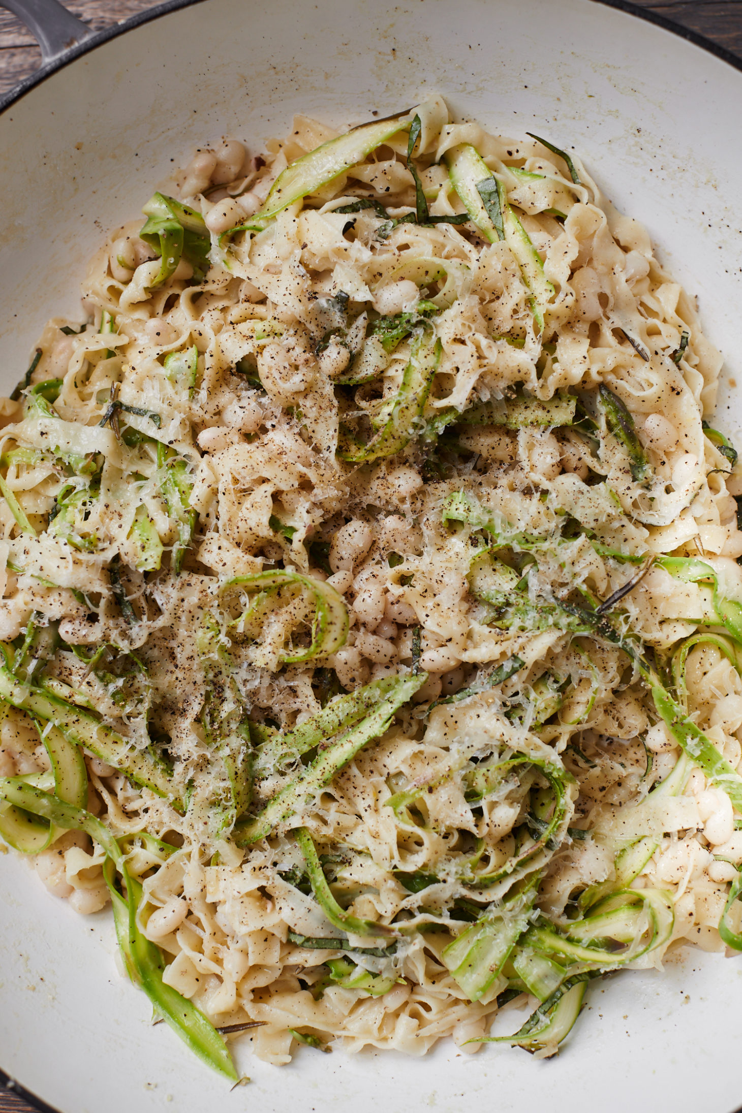 Close-up photo of pasta in a braiser tossed with shaved asparagus, white beans, basil, and parmesan