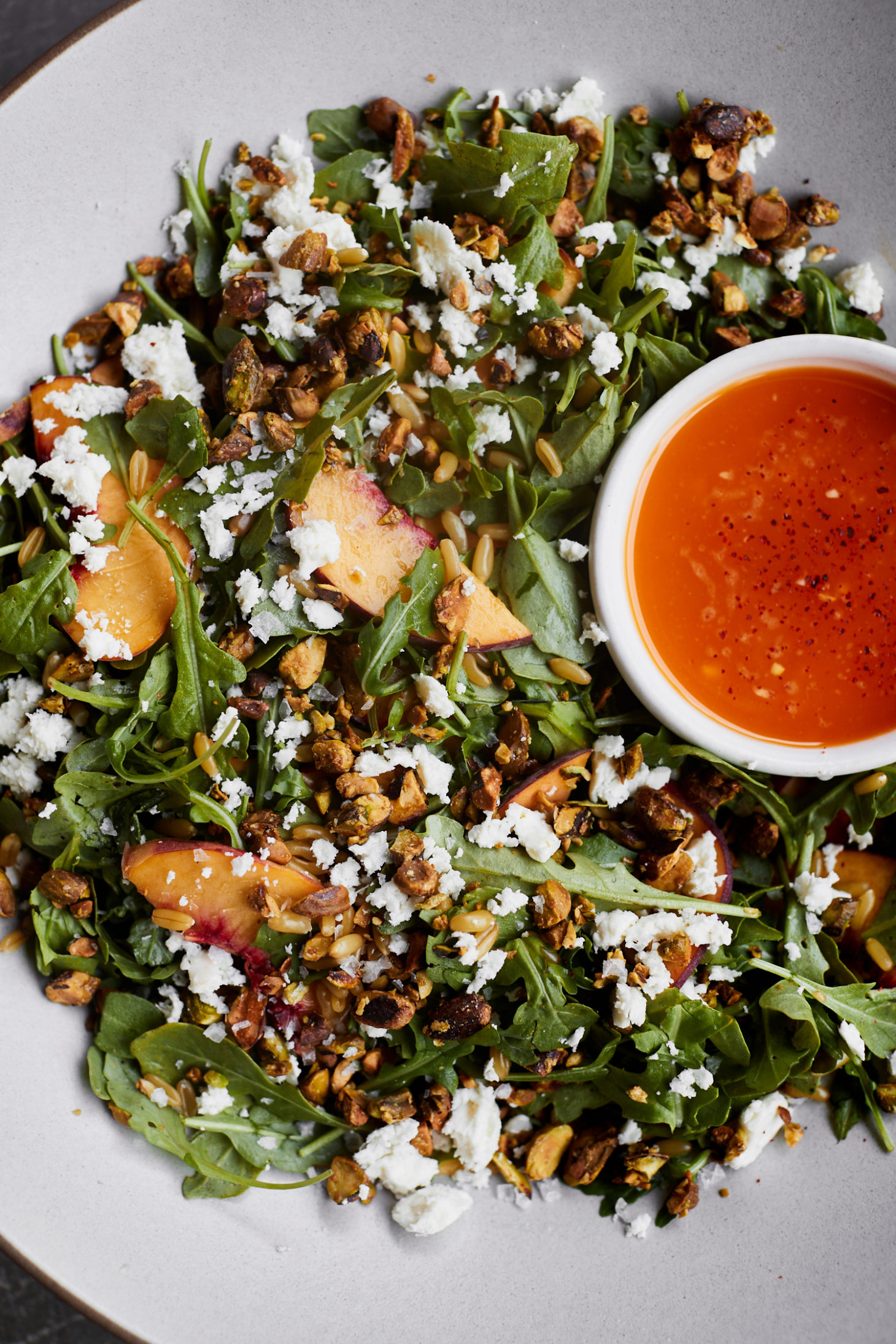 Close-up photo of a salad with peaches, pistachios, a chili dressing- all in a grey bowl.