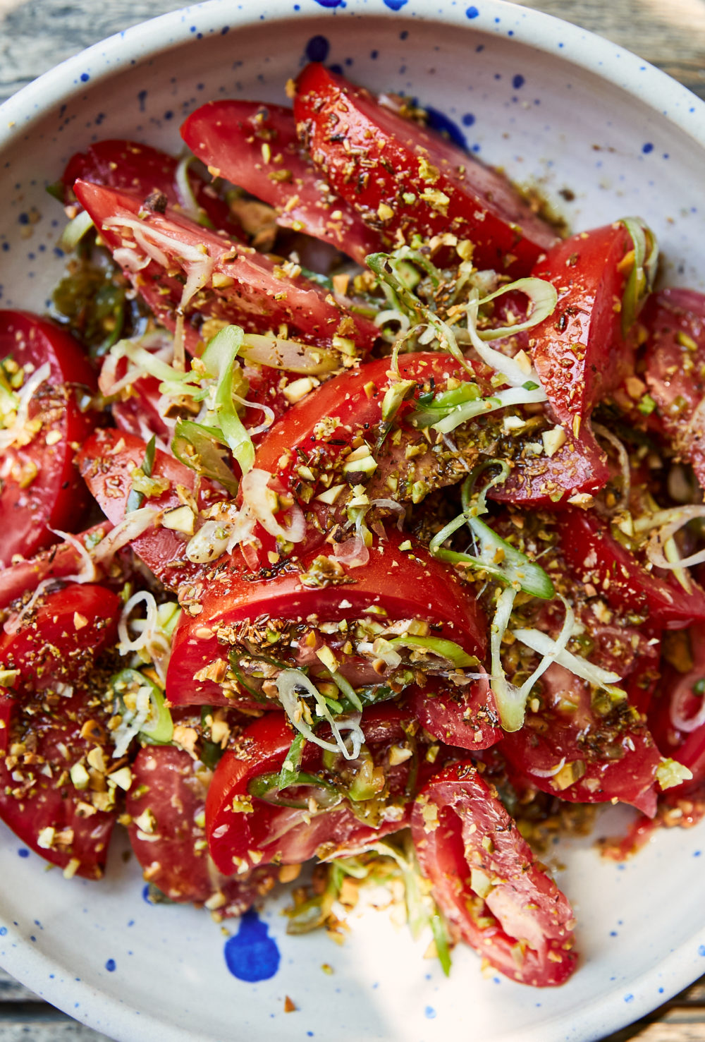 Close-up photo of tomato salad with fresh scallions in a bowl with blue speckles.